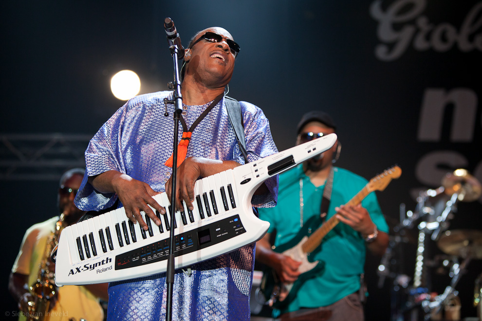 Stevie Wonder playing on shoulder synthesizer.